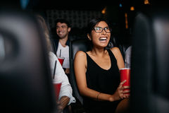 Woman watching movie in theater. Shot of young women sitting in multiplex movie theater watching movie and laughing Stock Photography