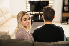 Woman watching movies with her boyfriend. Portrait of a beautiful young Hispanic women watching movies at home with her boyfriend Stock Photo