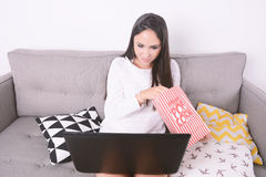 Woman watching movies with laptop. Beautiful young woman watching movies with laptop and eating popcorn. Indoors Royalty Free Stock Photo