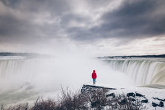 Woman watching Niagara falls from a snowy ledge Stock Photos