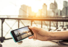 Woman watching photo of New york city skyline on the smart phone. Royalty Free Stock Photo