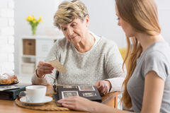 Woman watching photographs with grandmother. Young women having coffee and watching old photographs with her grandmother royalty free stock photo