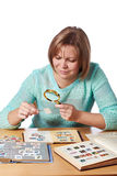 Woman watching postage stamps Royalty Free Stock Images