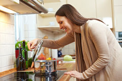 Woman watching pot. Woman in the kitchen watching food in a pot on the stove stock image