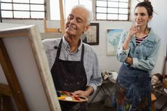 Woman watching while senior man painting on canvas. Woman watching while senior men painting on canvas in drawing class royalty free stock photo