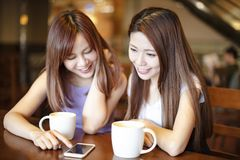 Woman watching the smart phone in coffee shop. Happy women watching the smart phone in coffee shop Royalty Free Stock Images