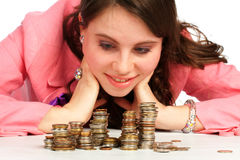 A woman watching stacks of coins Royalty Free Stock Photos