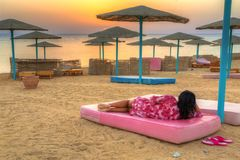 Woman watching sunrise on the beach of Red Sea. In Egypt Stock Photography