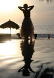 Woman watching sunset. Woman and her reflection in a pool by the ocean Stock Photography