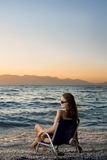 Woman watching sunset on the beach Stock Photography