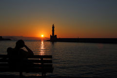 Woman watching sunset behind the lighthouse Royalty Free Stock Images