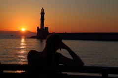 Woman watching sunset behind the lighthouse Stock Photography