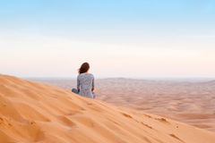 Woman watching the sunset in the desert sand Royalty Free Stock Photos
