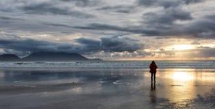 Woman watching sunset stock photos