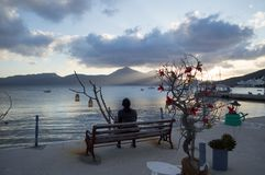 Woman Watching Sunset over Bay of Adamantas with Typical Whitewashed Houses, Milos, Greece stock image