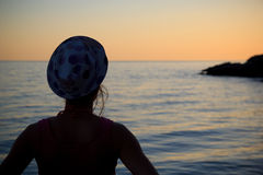 Woman watching the sunset by the sea. Sitting alone Stock Images