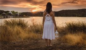 Woman watching the sunset with white dress and lantern royalty free stock photography