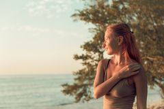 Woman watching sunset. Young woman watching as sun sets over Pacific Ocean Stock Photos