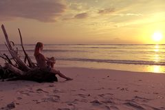 Woman watching sunset. Young woman watching as sun sets over Pacific Ocean Royalty Free Stock Images