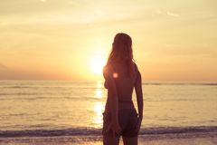 Woman watching sunset. Young woman watching as sun sets over Pacific Ocean Stock Photo