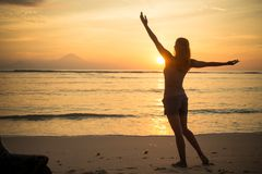 Woman watching sunset. Young woman watching as sun sets over Pacific Ocean Stock Photography