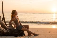 Woman watching sunset. Young woman watching as sun sets over Pacific Ocean Royalty Free Stock Image