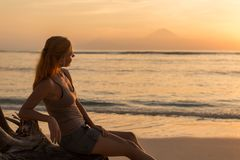 Woman watching sunset. Young woman watching as sun sets over Pacific Ocean Stock Images