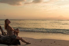 Woman watching sunset. Young woman watching as sun sets over Pacific Ocean Royalty Free Stock Photo