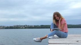 Woman watching at tablet while sitting near lake stock video