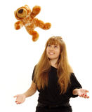 Woman watching teddy bear. A studio view of a young woman watching a teddy bear in the air as if throwing or catching the bear Stock Photo