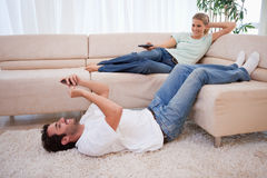 Woman watching television. Women watching television while her husband is using his cellphone in their living room Royalty Free Stock Photos