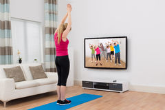 Woman Watching Television And Exercising At Home Royalty Free Stock Photos