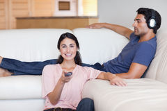 Woman watching television with her husband Stock Photos