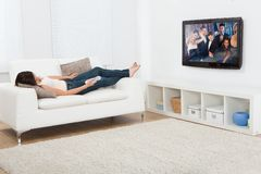 Woman watching television while lying on sofa Stock Image