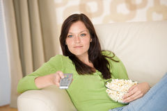 Woman watching television with popcorn Royalty Free Stock Images