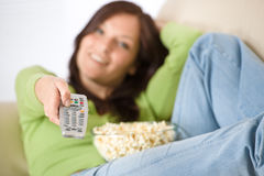 Woman watching television with popcorn in lounge Stock Photo