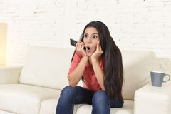 Woman watching television sitting at sofa couch happy excited enjoying comedy movie. Young beautiful Spanish woman in jeans home alone watching television Stock Images