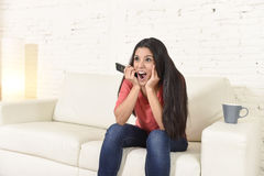 Woman watching television sitting at sofa couch happy excited enjoying comedy movie. Young beautiful Spanish woman in jeans home alone watching television Royalty Free Stock Photography