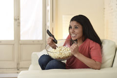 Woman watching television sitting at sofa couch happy excited enjoying comedy movie Royalty Free Stock Photography