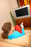 Woman watching tv. Sitting on sofa Royalty Free Stock Images