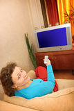 Woman watching tv. Sitting on sofa Stock Photos