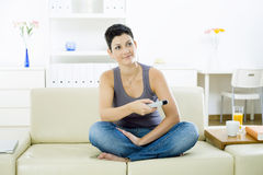 Woman watching TV. Young woman sitting on sofa at home watching TV Royalty Free Stock Image