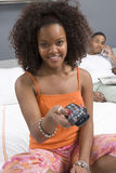 Woman Watching TV In Bedroom. Portrait of happy young women holding TV remote with men in background Stock Photos