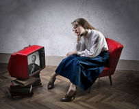 Woman watching tv. Bored woman watching a tv show Royalty Free Stock Images