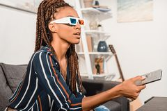 Woman watching tv in 3d goggles. Beautiful african american woman watching tv in 3d goggles stock photo