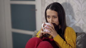 Woman Watching TV and Drinking Tea. On the couch stock video footage