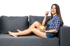 Woman watching TV and eating chips on white background. Young woman watching TV and eating chips Royalty Free Stock Images