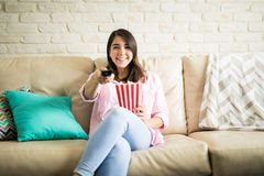 Woman watching tv and eating a snack Royalty Free Stock Photos