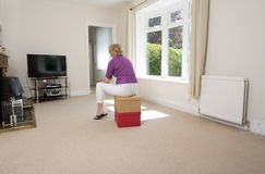Woman watching tv in an empty room Stock Photography