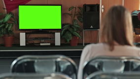 Woman watching TV with green screen. In the empty conference hall of cruise ship stock video footage